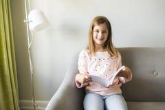 Libro de lectura de la muchacha en el hogar de Sofa In Living Room At foto de archivo libre de regalías