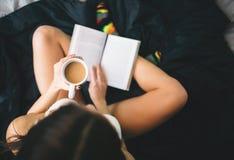 Libro de lectura de la muchacha y café de consumición en la cama La opinión superior la mujer joven leyó un libro en ropa de cama Foto de archivo
