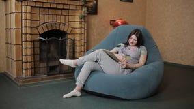 Libro de lectura de la mujer embarazada mientras que se sienta en el sofá almacen de metraje de vídeo