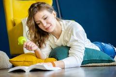 Libro de lectura de la mujer en casa y poniendo en el piso al lado de la butaca amarilla foto de archivo