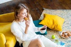 Libro de lectura de la mujer en casa y sentándose en el piso al lado de la butaca amarilla imagen de archivo libre de regalías
