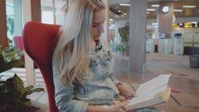 Libro de lectura de la mujer en el aeropuerto almacen de video