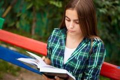 Libro de lectura de la mujer joven al aire libre imagen de archivo libre de regalías