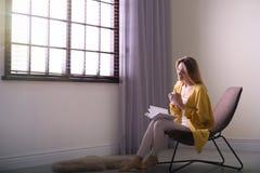 Libro de lectura de la mujer joven cerca de la ventana con las persianas en casa fotografía de archivo libre de regalías