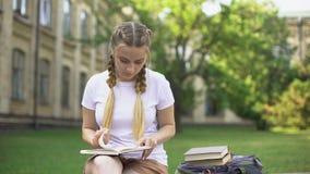 Libro de lectura de la mujer joven en banco en el campus, preparando la preparación, educación metrajes