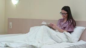 Libro de lectura de la mujer joven en cama antes del sueño y de reír imagen de archivo libre de regalías