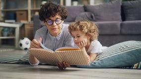 Libro de lectura de la mujer joven y del niño pequeño de la familia feliz que miente en la manta en casa almacen de metraje de vídeo