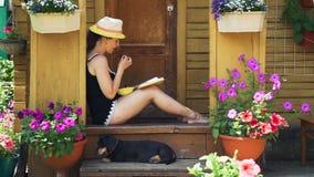 Libro de lectura de la mujer joven y fresas de la consumición almacen de metraje de vídeo
