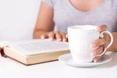 Libro de lectura de la mujer joven y taza de la tenencia de escritorio del café en casa imagen de archivo