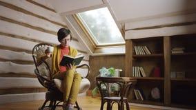 Libro de lectura de la mujer mientras que bebe el café en ático almacen de video