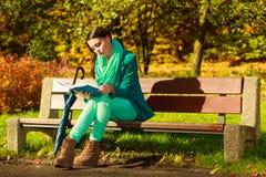 Libro de lectura de la mujer que se sienta en banco en parque Foto de archivo libre de regalías