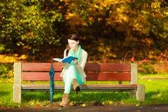Libro de lectura de la mujer que se sienta en banco en parque Imágenes de archivo libres de regalías