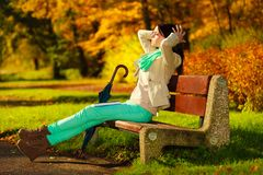 Libro de lectura de la mujer que se sienta en banco en parque Imagenes de archivo