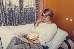 Libro de lectura de la mujer y palomitas envejecidos medios de la consumición fotos de archivo