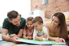Libro de lectura de la pareja de los jóvenes con los niños en casa Fotografía de archivo libre de regalías