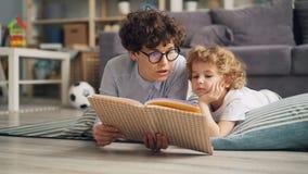 Libro de lectura de la señora joven a su hijo que discute la historia que miente en piso en casa metrajes