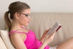 Libro de lectura de las lentes de la mujer que lleva joven en el sofá en casa Foto de archivo libre de regalías