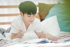 Libro de lectura lindo asiático del niño pequeño con la cara de la sonrisa Foto de archivo libre de regalías