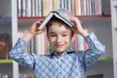 Libro de lectura lindo del muchacho en biblioteca Fotos de archivo