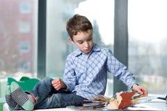 Libro de lectura lindo del muchacho en biblioteca Imagen de archivo