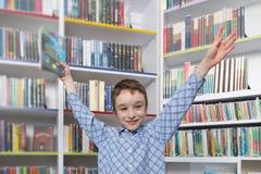 Libro de lectura lindo del muchacho en biblioteca Imagenes de archivo