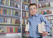 Libro de lectura lindo del muchacho en biblioteca Imágenes de archivo libres de regalías