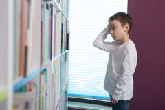 Libro de lectura lindo del muchacho en biblioteca Fotos de archivo libres de regalías