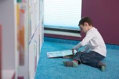 Libro de lectura lindo del muchacho en biblioteca Fotografía de archivo