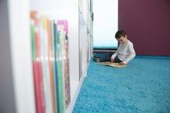 Libro de lectura lindo del muchacho en biblioteca Imagen de archivo libre de regalías