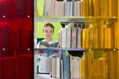 Libro de lectura lindo del muchacho en biblioteca Foto de archivo libre de regalías