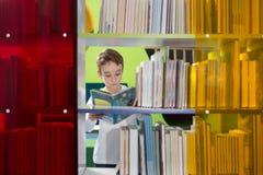 Libro de lectura lindo del muchacho en biblioteca Fotografía de archivo libre de regalías