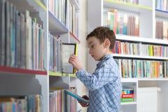 Libro de lectura lindo del muchacho en biblioteca Foto de archivo