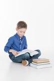 Libro de lectura lindo del muchacho en blanco Foto de archivo libre de regalías
