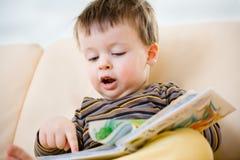 Libro de lectura lindo del niño pequeño en el sofá Imagenes de archivo