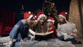 Libro de lectura lindo elegante de los niños mientras que se relaja en el cuarto cerca del árbol de navidad almacen de metraje de vídeo