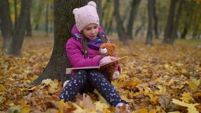 Libro de lectura lindo de la muchacha debajo del árbol en parque del otoño almacen de metraje de vídeo