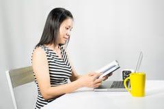 Libro de lectura lindo de la mujer en el escritorio del trabajo foto de archivo libre de regalías