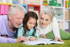 Libro de lectura de los abuelos con la pequeña nieta fotos de archivo libres de regalías
