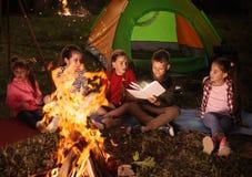 Libro de lectura de los niños con la linterna al aire libre Campamento de verano imágenes de archivo libres de regalías