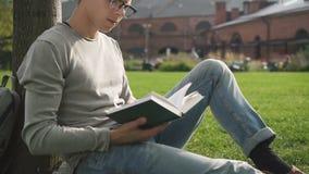 Libro de lectura masculino del estudiante universitario que se sienta en la tierra del campus almacen de metraje de vídeo