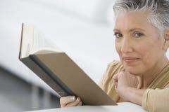 Libro de lectura mayor de la mujer en el sofá Fotos de archivo libres de regalías