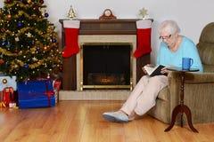 Libro de lectura mayor de la mujer en sala de estar de la Navidad Imagen de archivo