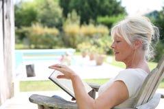 Libro de lectura mayor de la mujer por la piscina Imagen de archivo