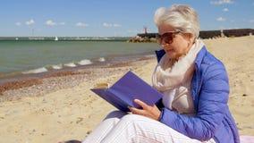 Libro de lectura mayor feliz de la mujer en la playa del verano metrajes