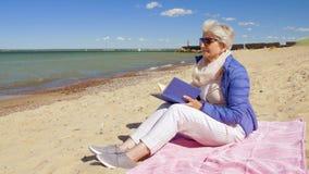 Libro de lectura mayor feliz de la mujer en la playa del verano almacen de metraje de vídeo