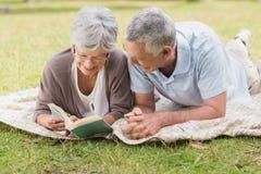 Libro de lectura mayor relajado de los pares mientras que miente en parque Foto de archivo