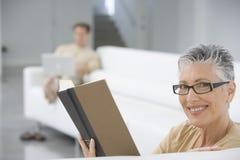 Libro de lectura mayor sonriente de la mujer en el sofá foto de archivo libre de regalías