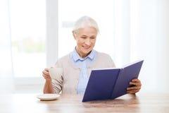 Libro de lectura mayor sonriente feliz de la mujer en casa Imágenes de archivo libres de regalías