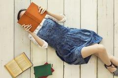 Libro de lectura mientras que miente en piso Imagen de archivo libre de regalías