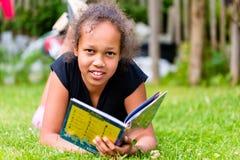 Libro de lectura negro de la muchacha en prado fotos de archivo libres de regalías